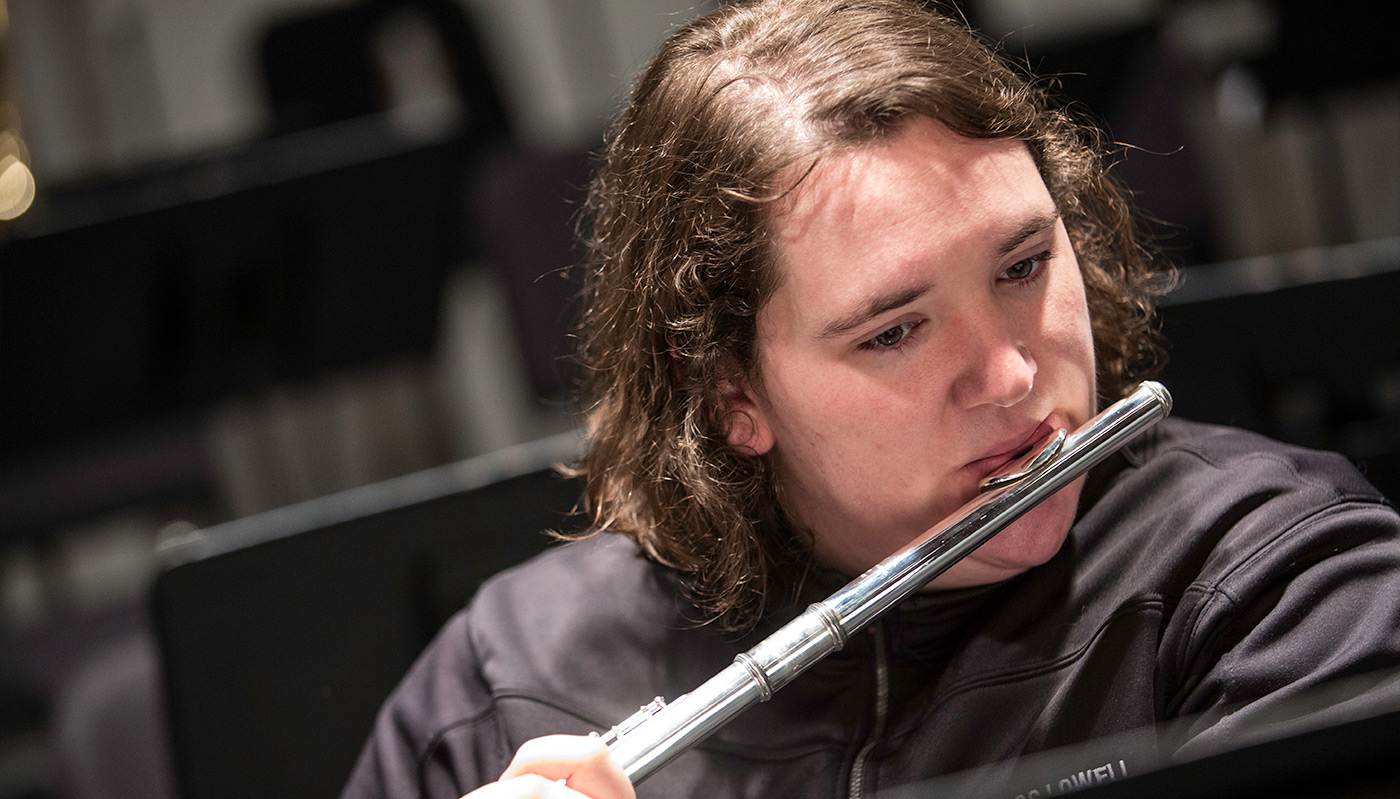 A male student playing the flute.