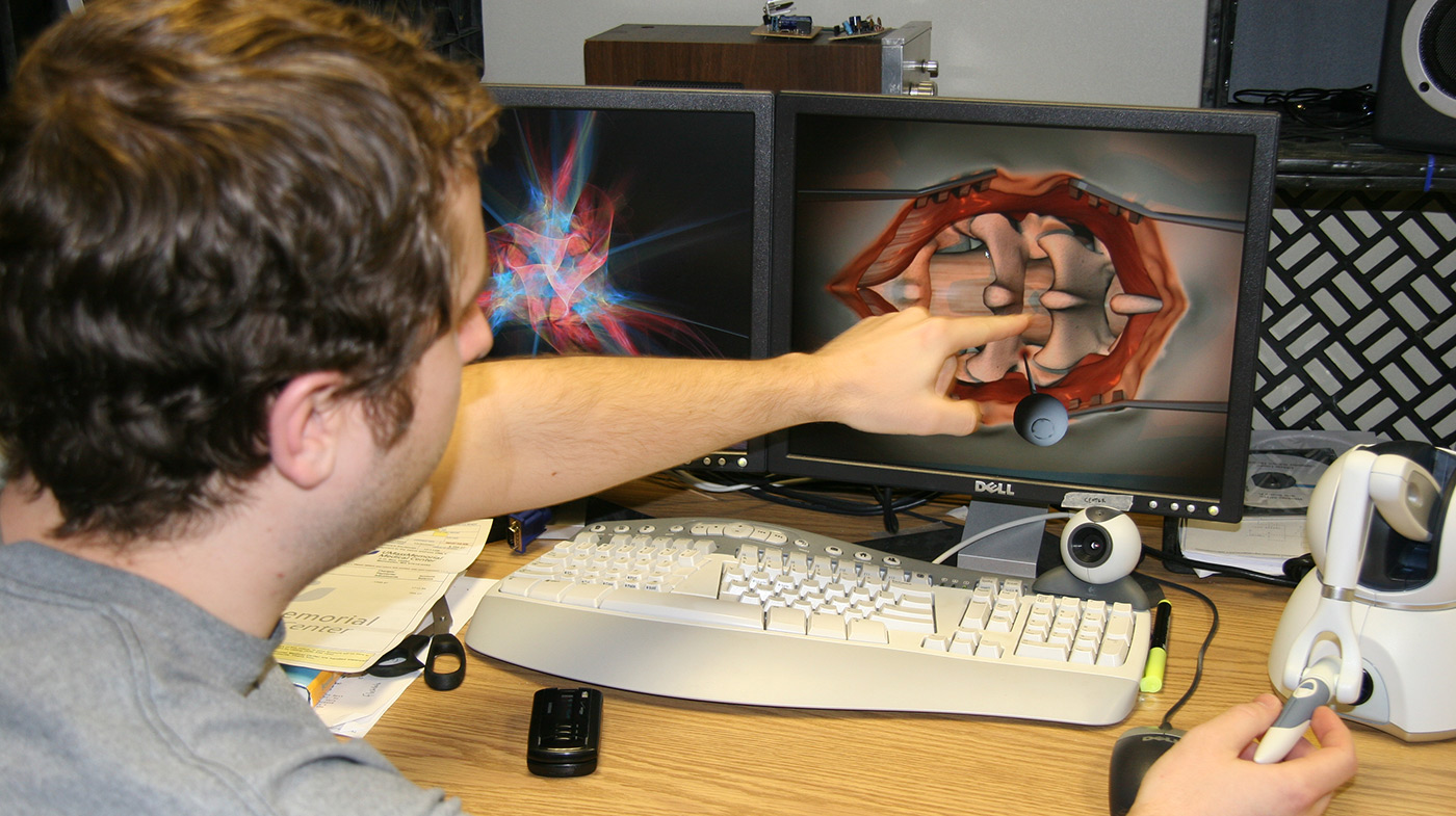 male-student-pointing-at-model-on-computer-screen