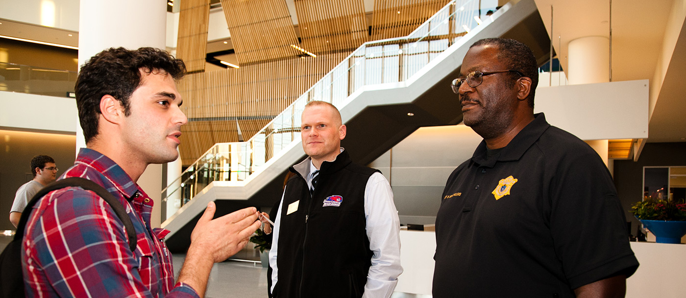 "A student talks with UMass Lowell Police Chief Randy Brashears and Joel McCarthy of Residence Life during a ""Coffee with a Cop"" event at University Crossing."