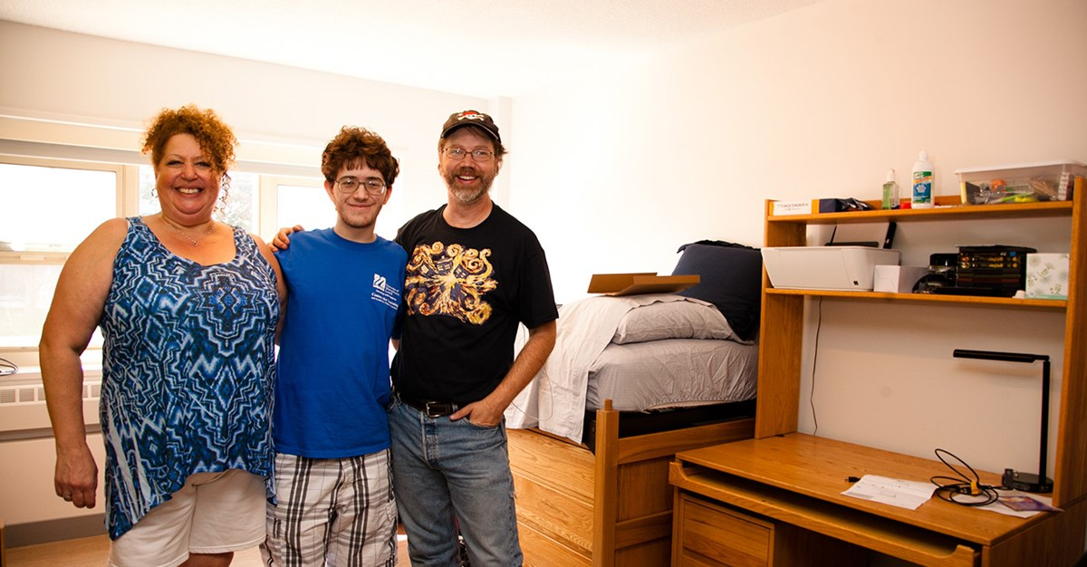 male-student-poses-with-parents-in-room