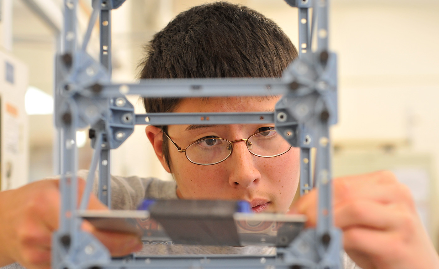 A male UMass Lowell student seen through the other side of his bridge model.