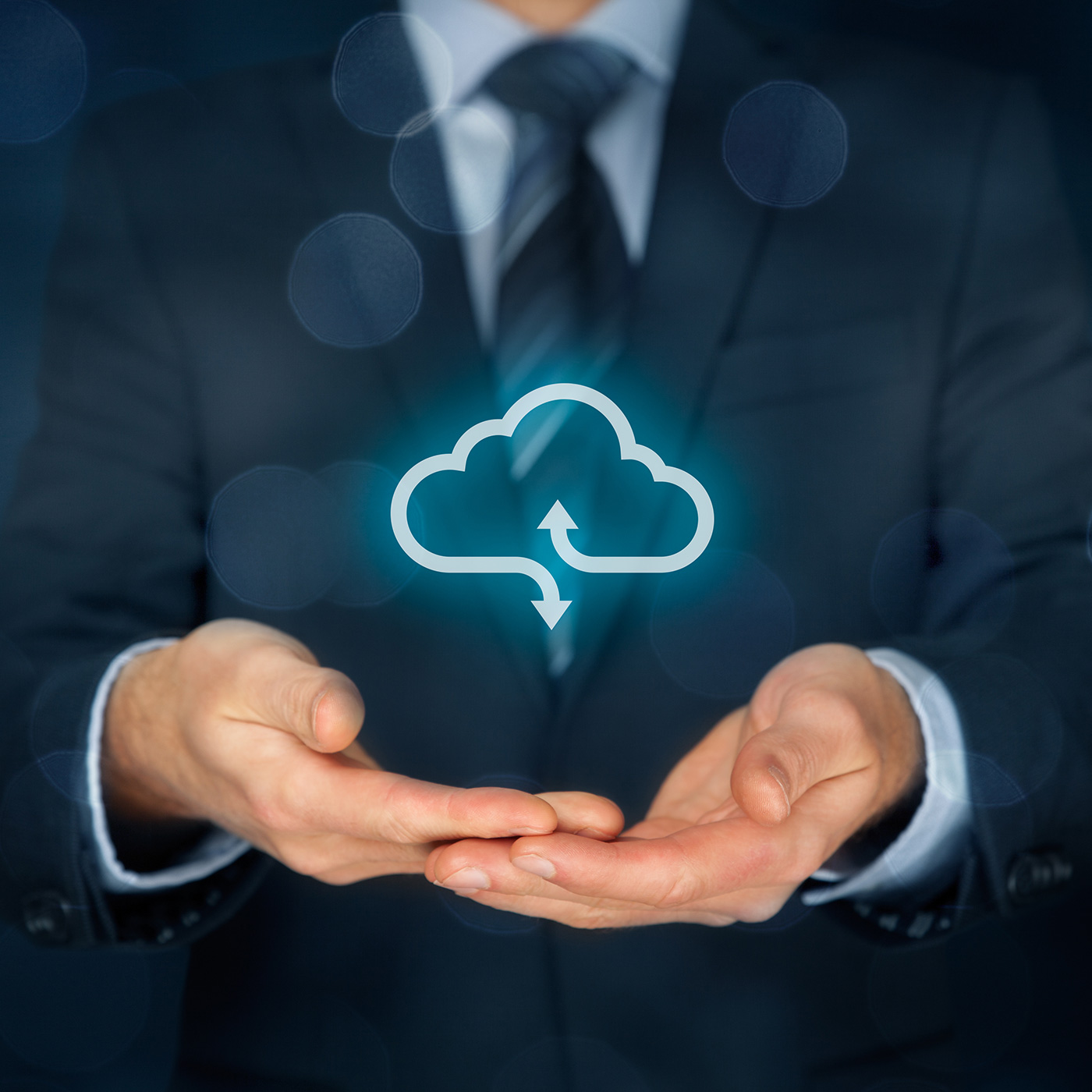 A stock image showing a man in a suit with his hands out and a symbol for cloud computing just above his hands.