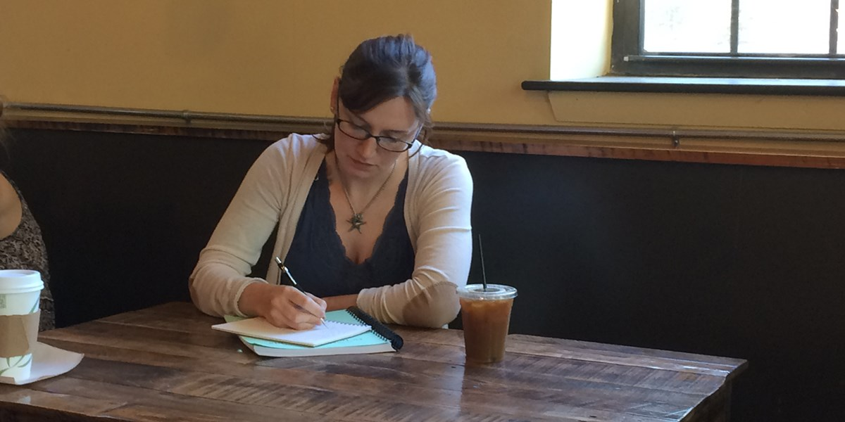 Mary Everett writes in a notebook at a table at a cafe