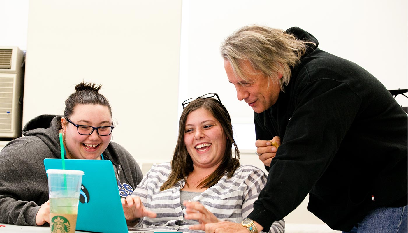 Two female students with Drew Hayden Taylor, author and playwright, during master class