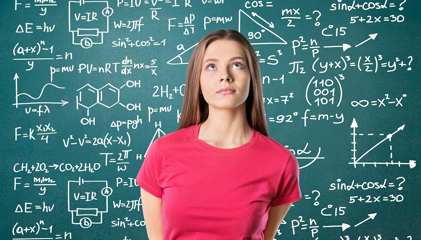 woman in front of blackboard with math, science formulas