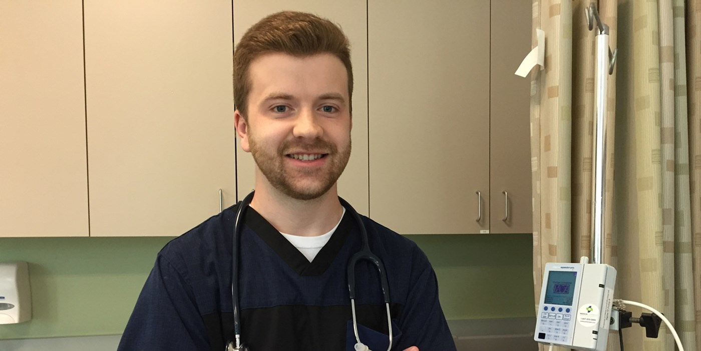 Matthew Fowler wearing scrubs and a stethoscope in a nursing simulation lab at UMass Lowell