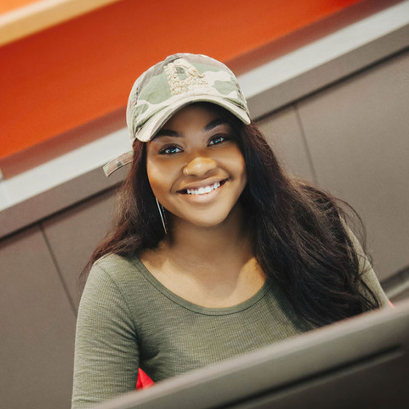 female student with baseball cap smiling