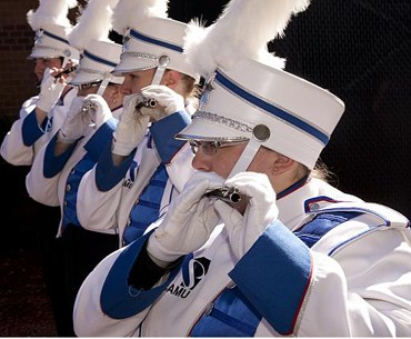 Four marching band students lined up horizontally, each playing the flute.