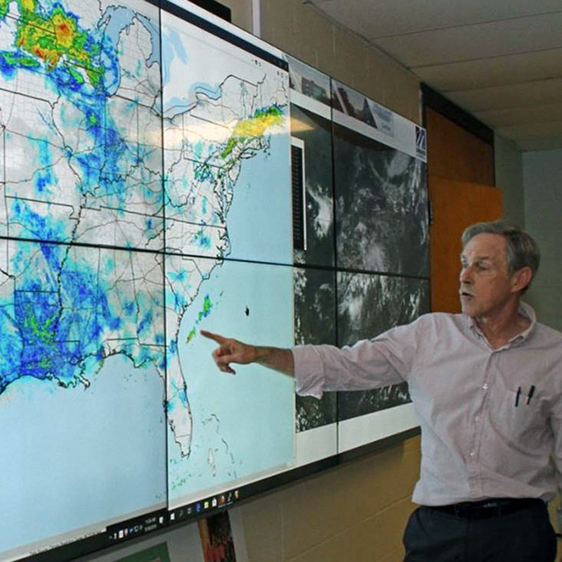 Professor Frank Colby of the EEAS department pointing to large, interactive weather monitor