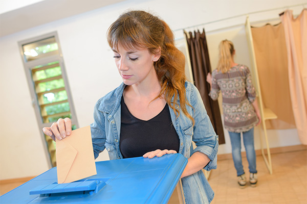 Young woman putting paper ballot into ballot box