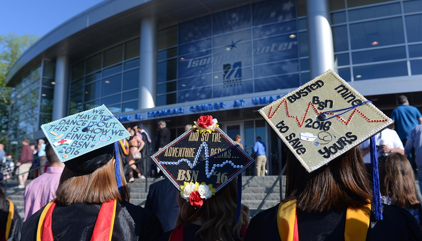 Three decorated mortarboards on heads of students outside Tsongas Center
