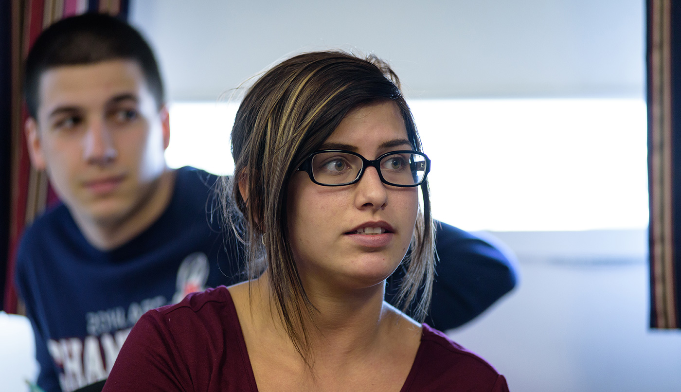 A female UMass Lowell Manning School of Business students looks on during a class.