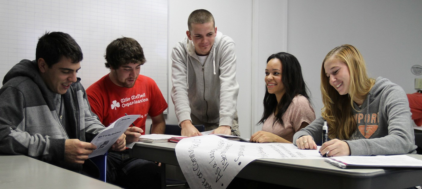 Three male and two female UMass Lowell Manning School of Business students working on a project together.
