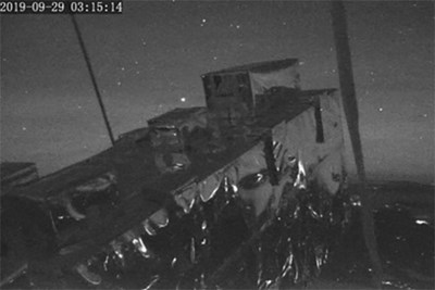 Black and white photo fromPICTURE-C of boxes on in foreground and meteor in background.