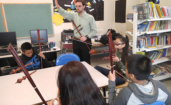 music-education-male-teacher-young-students-instruments-classroom