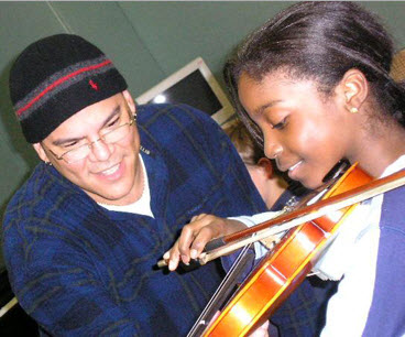 Man in winter hat teaching young girl the violin.