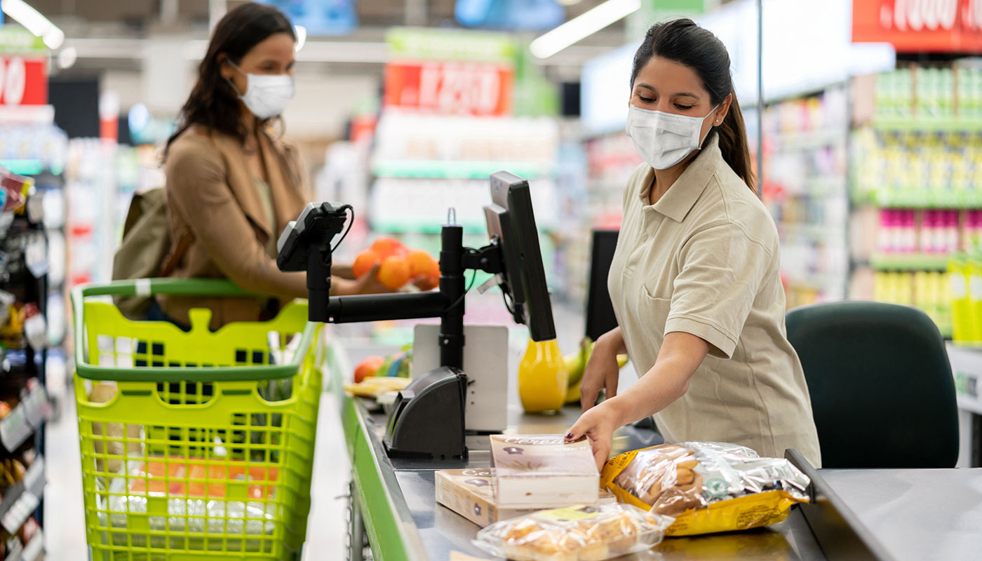 Masked supermarket worker checks out customer