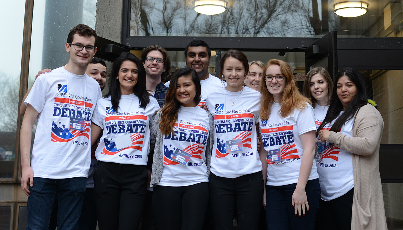 11 students wearing UMass Lowell-Boston Globe debate T-shirts in group shot in front of Durgin Hall