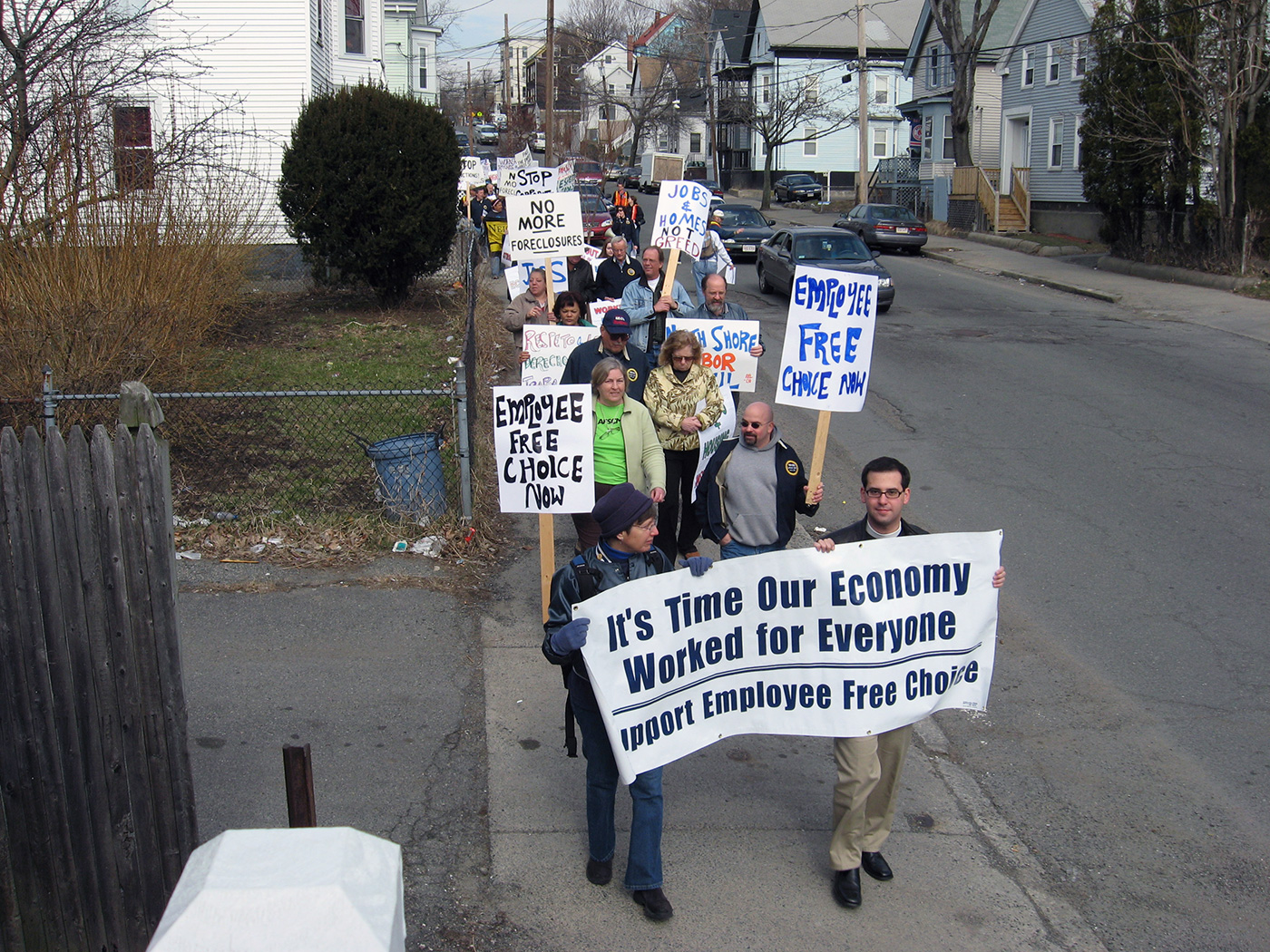 "Workers carry signs and banners that say ""it's time our economy worked for everyone"""
