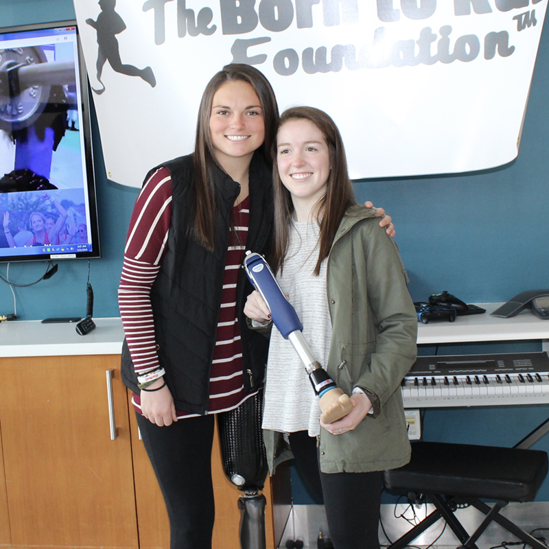 Noelle Lambert poses with 24-year-old Emma Graham and her waterproof prosthetic, donated by Born to Run Foundation