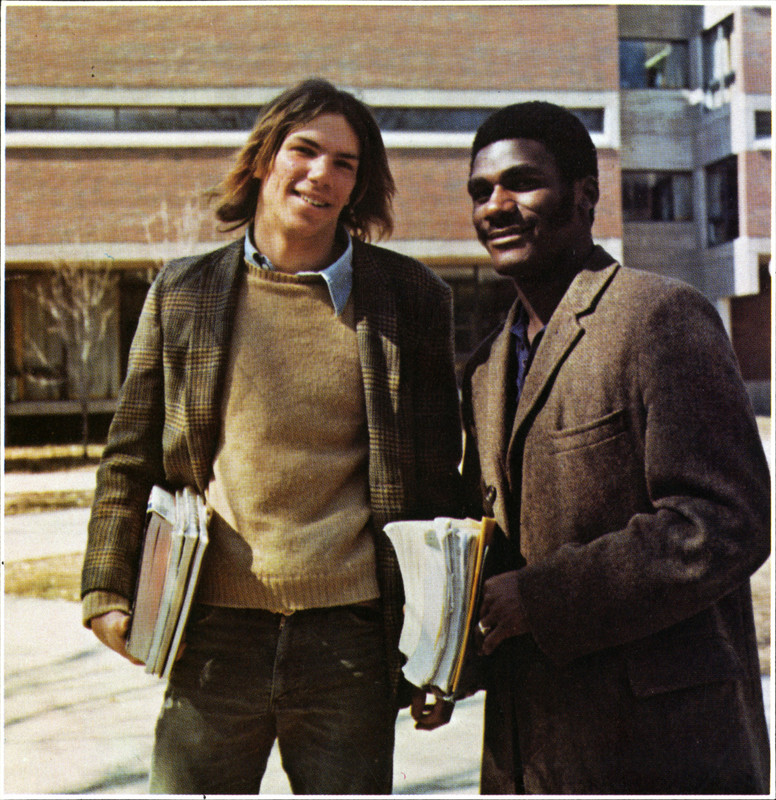 Two male students holding books outside of a building on UML's North Campus