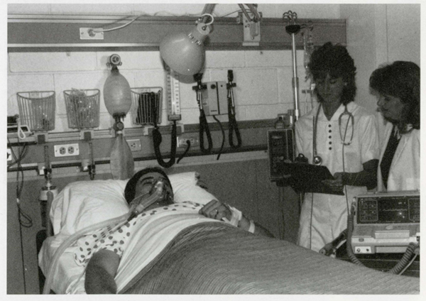 "Two nursing students look over a ""patient"" in a nursing intensive care unit lab in 1989"