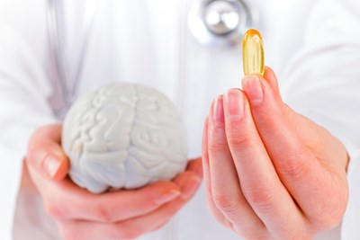 Doctor holding model of brain in one hand and omega-3 capsule in other