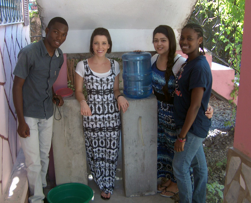 One male young adult and three female young adults posing for a picture next to a water jug with a hose for dispensing.