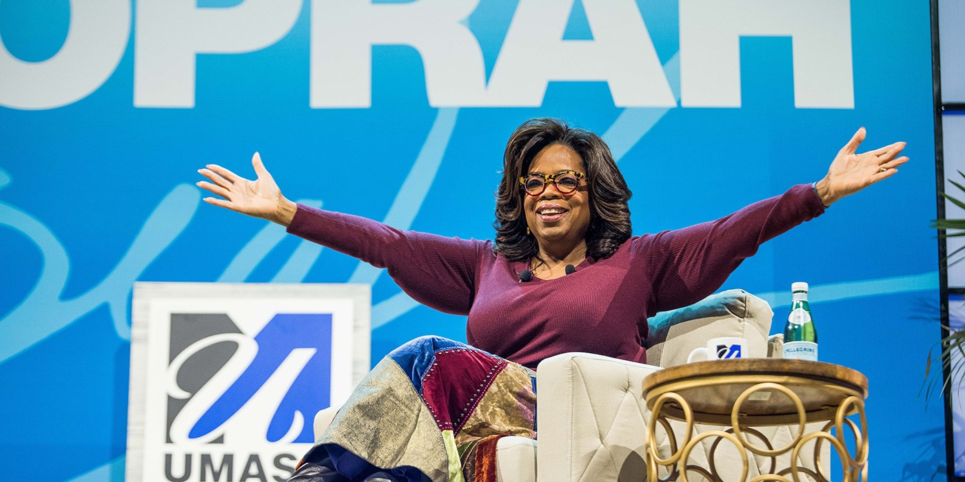 Oprah Winfrey spreads her arms wide while seated during the UMass Lowell Chancellor's Speaker Series