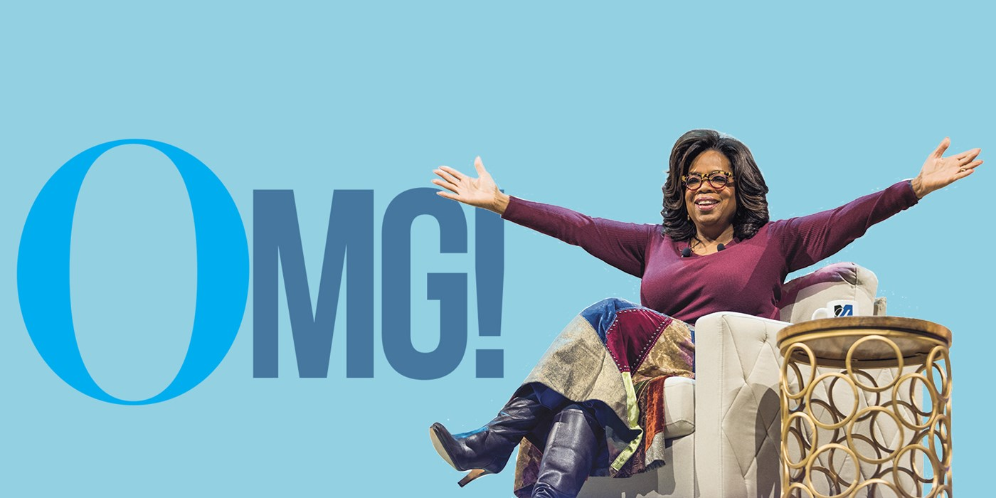 "Oprah sitting in a chair smiling with her arms wide next to a table with a UML mug against a blue background that says ""OMG!"""