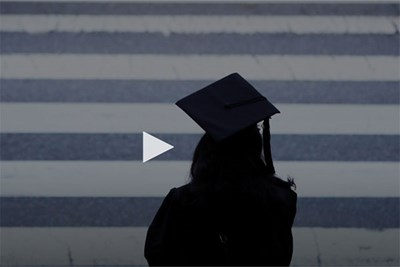 Silhouette of graduate in front of black and white stripes