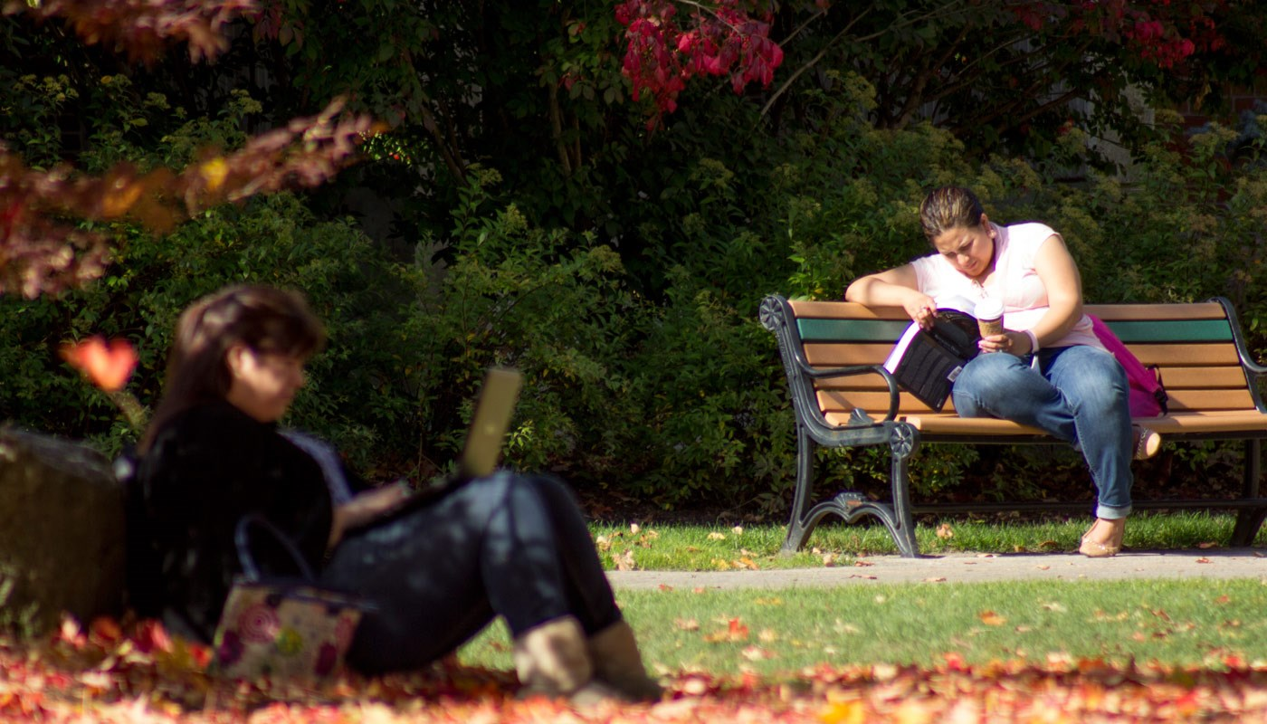 Two female students reading outdoors