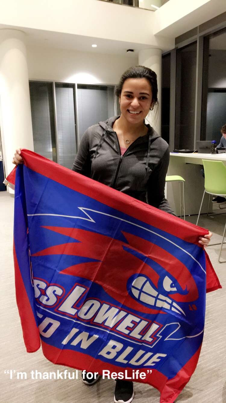 "UMass Lowell student holding flag is ""thankful for Res Life"""