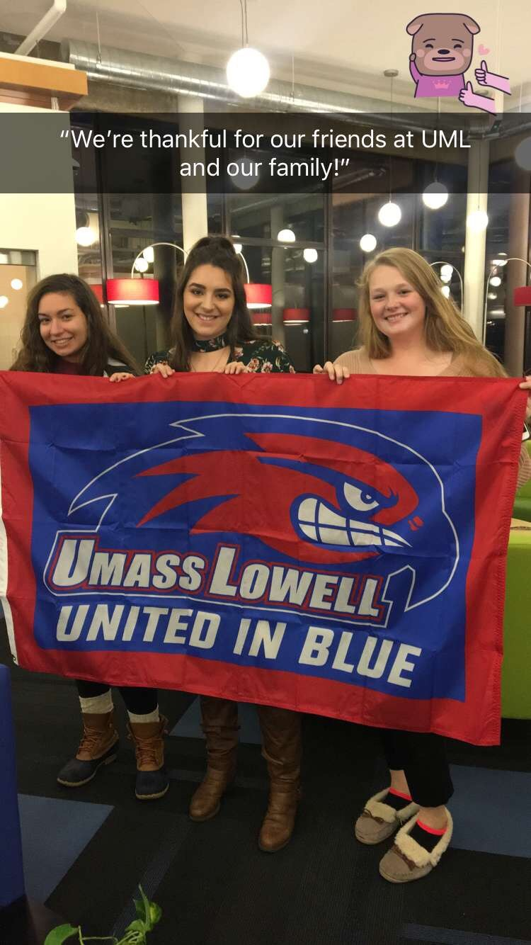 "Three UMass Lowell students holding ""United in Blue"" flag are thankful for their friends at UML and their families"