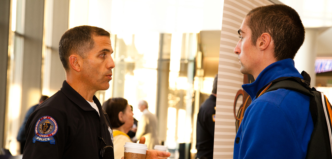 "A UMass Lowell police officer chats with a student during the ""Coffee with a Cop"" event."