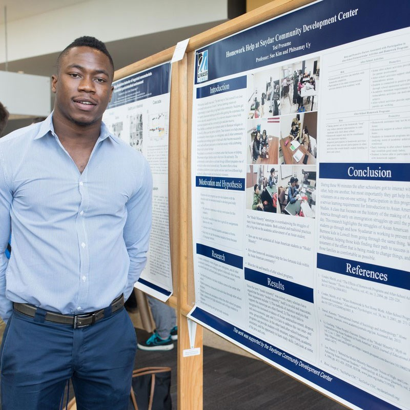 Young black man stands in front of research poster