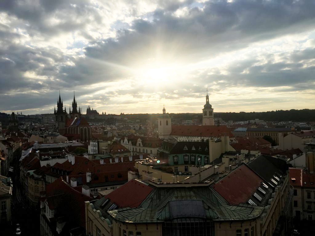 The sun shines through clouds as seen from the top of a tower ion Prague.