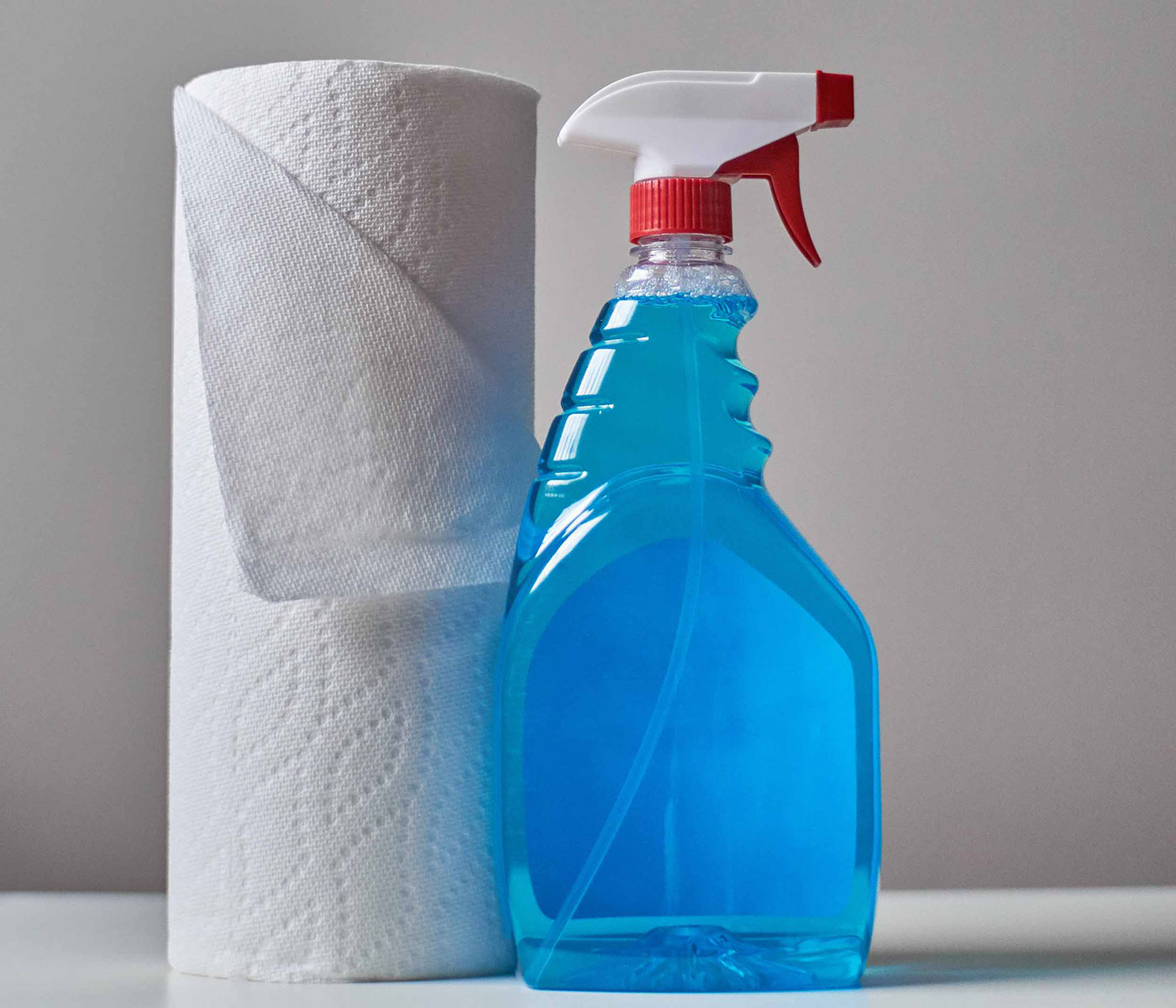 Purchasing-Cleaning and Janitorial Products: a roll of paper towels is placed next to a spray bottle filled with a blue cleaning product.