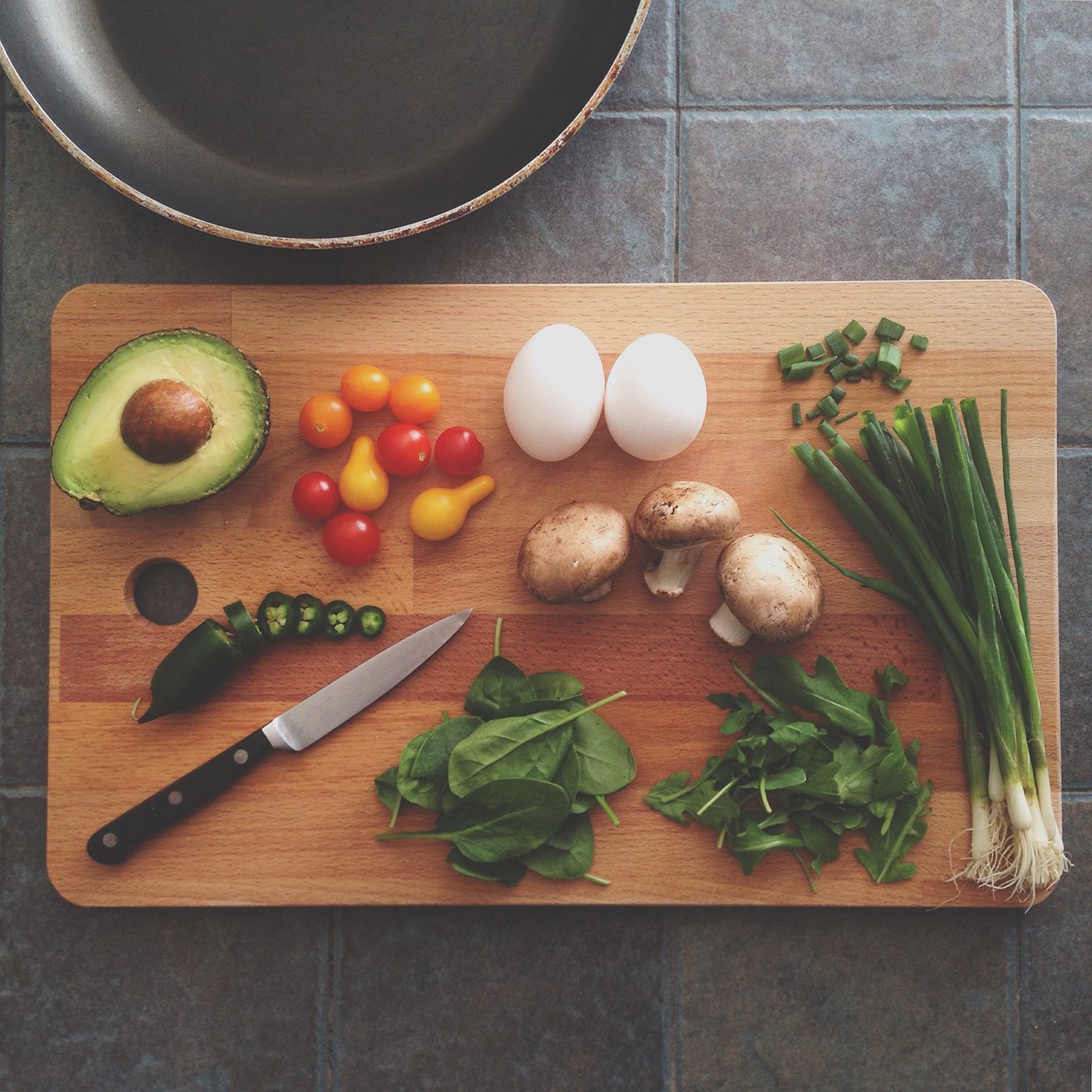 Purchasing-Food and Beverages: a wooden cutting board with vegetables and fruits on top of it, as well as a knife ready to cut them to make them into a dish.