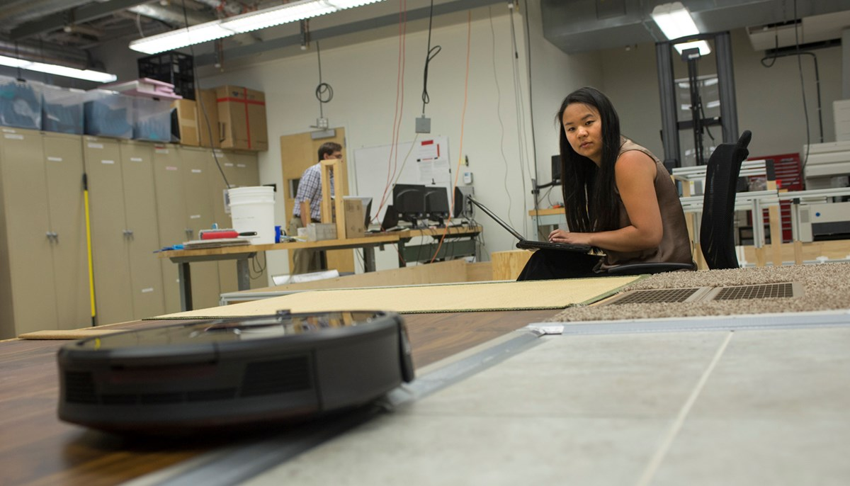 UMass Lowell student Qiana Curcuru works at iRobot designing and building a friction test track for prototypes of the next generation of Braava Jets, the company's floor-mopping robots