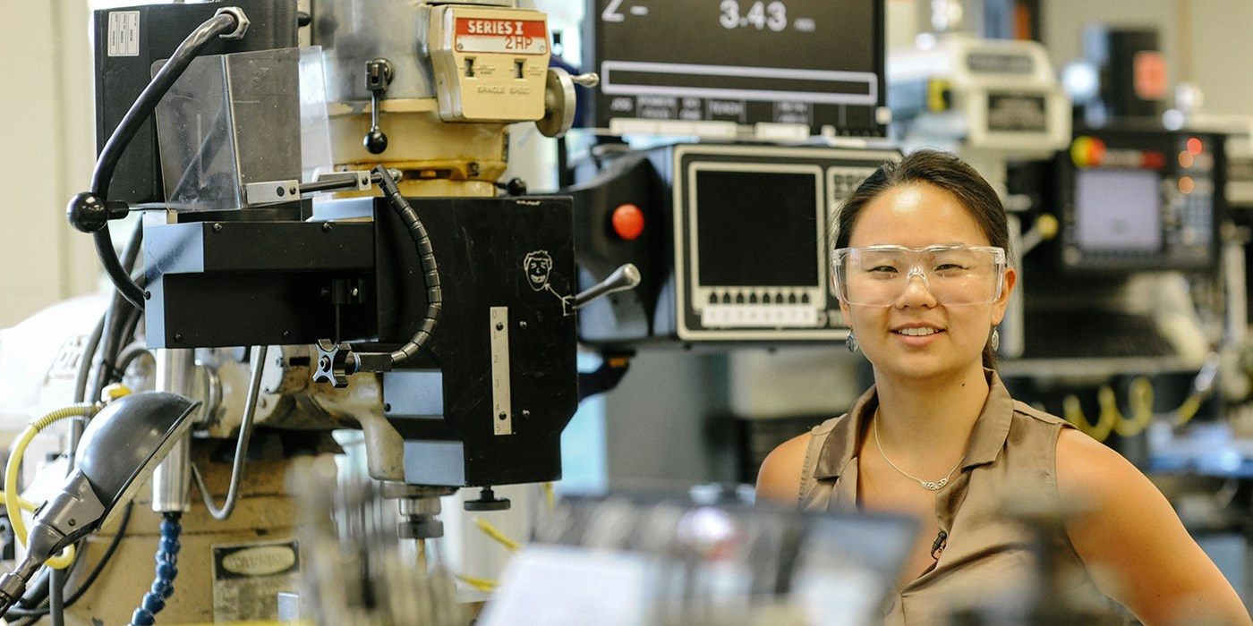 Mechanical Engineering major Qiana Curcuru standing in front of equipment at iRobot, where she co-oped.