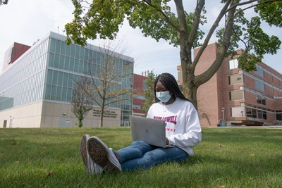 Young black woman wearing mask, seated on grass, working on laptop on her lap