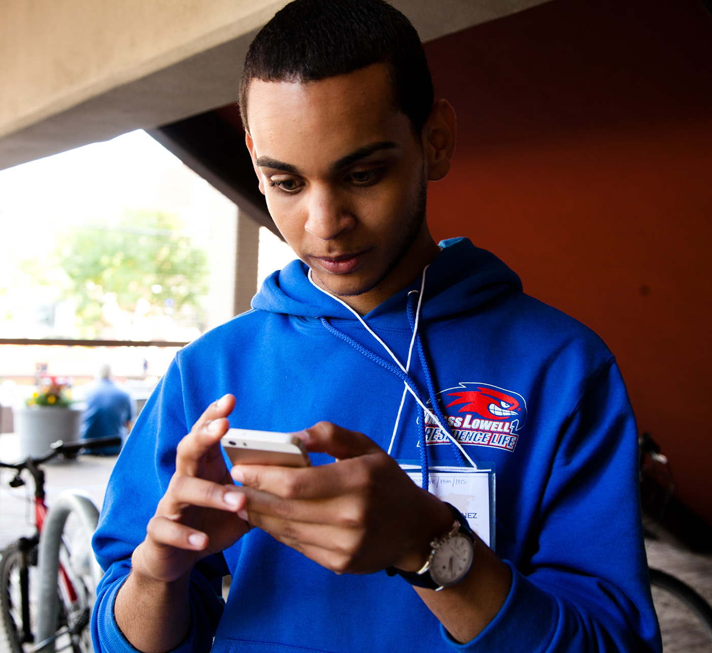 A Residence Life staffer checks his smart phone during East Campus move-in.
