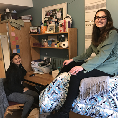 One female student sits at her desk in her room in her residence hall and her roommate sits on a bed, smiling at the camera