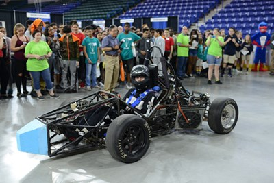 River Hawk Racing team brings their car out in front of a crowd and Rowdy at an event at the Tsongas Center