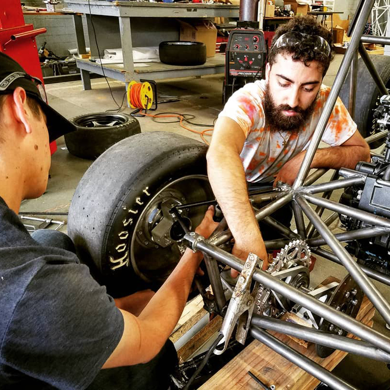 Two students from UML's Society of Automotive Engineers work on building a Formula One racecar