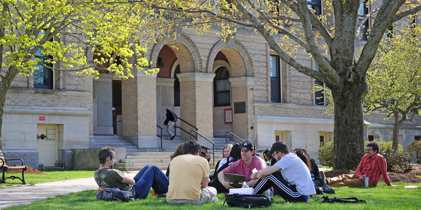 Group of students sit on the lawn in circle with laptops in front of Coburn Hall