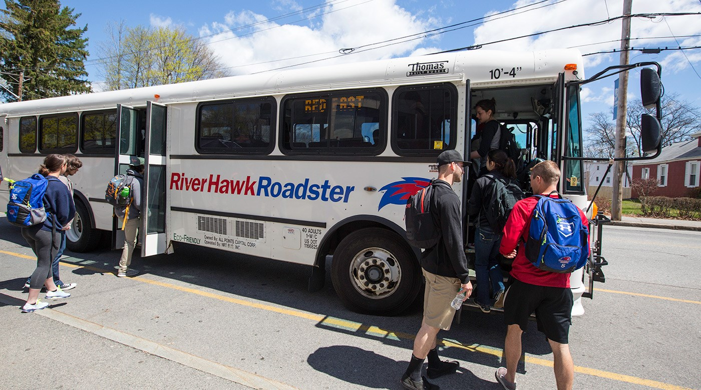 Students getting on a UMass Lowell River Hawk Roadster bus.