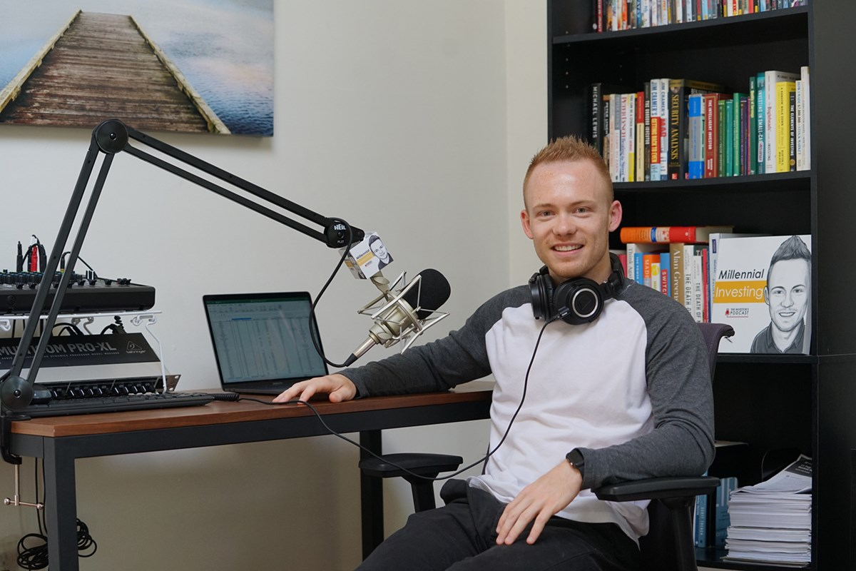 "Robert Leonard sits at a laptop and microphone with headphones around his neck ready to record his podcast, ""Millennial Investing"""