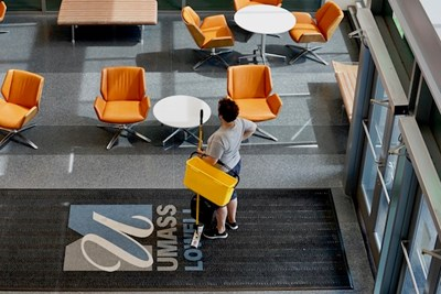 A housekeeping staff member stands inside the business school